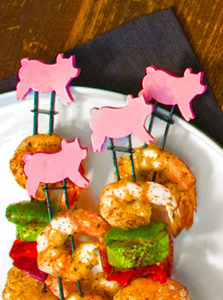 Pig themed grilling skewers with shrimp and vegetables plated with napkin photography by Bayard Heimer